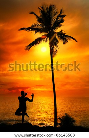 Yoga lord krishna pose by Man in silhouette with palm tree nearby outdoors at ocean and sunset background. Vagator beach, Goa, India - stock photo