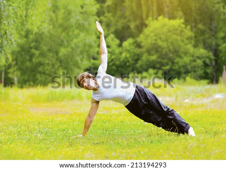 Yoga man doing exercise outdoors on the grass - stock photo