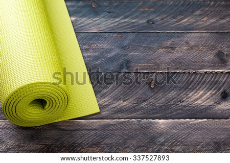 Yoga mat on a wooden background. Equipment for yoga. Concept  healthy lifestyle. Lots of copyspace. Selective focus - stock photo