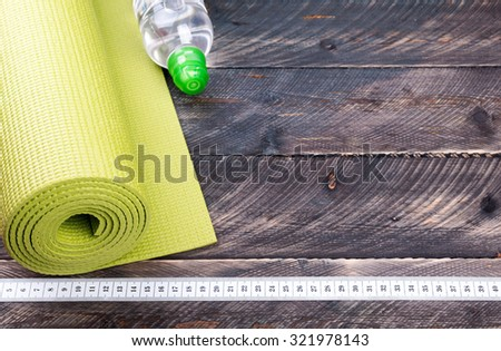 Yoga mat, water bottle and centimeter on a wooden background. Equipment for yoga. Concept  healthy lifestyle. Selective focus - stock photo