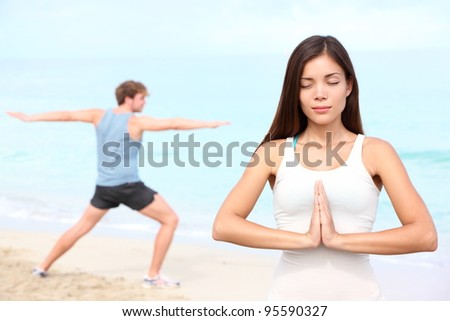 Yoga meditation couple meditating outdoor on beach. Young happy interracial couple during outdoor workout. Beautiful young Asian fitness woman and Caucasian man. - stock photo