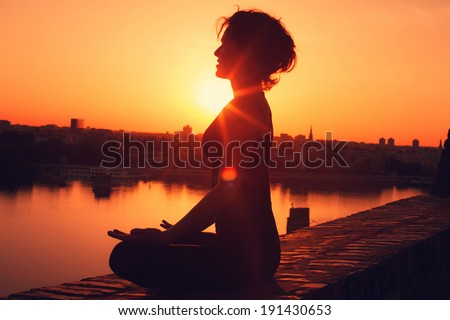 Yoga meditation during the sunset  - stock photo