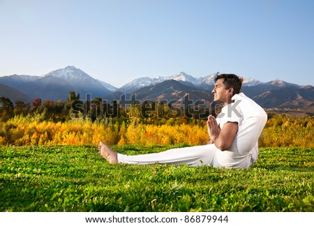 Yoga meditation eka pada shirasana foot behind the head pose by concentrate Indian Man in white cloth in the morning at mountain and blue sky background. Free space for text - stock photo