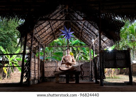 Yoga meditation in lotus pose by Caucasian man in yoga hall at banana trees background in Varkala, Kerala, India - stock photo