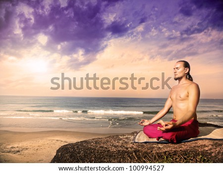 Yoga meditation in lotus pose by man with long hair in red trousers on the cliff near the ocean in Varkala, Kerala, India - stock photo