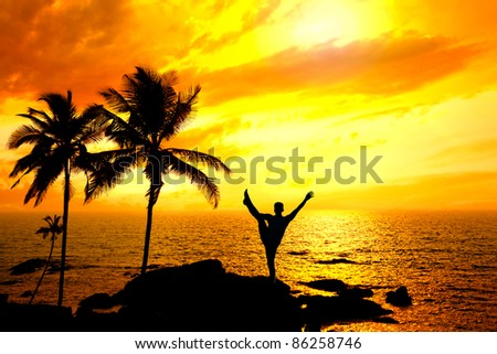 Yoga Natarajasana dancer balancing pose by Man in silhouette with palm tree nearby outdoors at ocean and sunset background. Vagator beach, Goa, India - stock photo