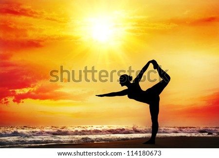 Yoga natarajasana dancer pose by woman in silhouette with dramatic sunset sky background. Free space for text - stock photo