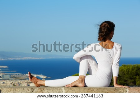Yoga on high altitude with big city on background, young woman seated in yoga pose on amazing city background, woman meditating yoga and enjoying sunny evening, woman makes yoga on mountain hill - stock photo