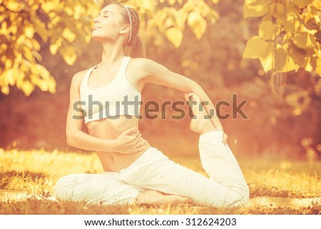 Yoga outdoors in warm autumn sunny park. Concept of healthy lifestyle and relaxation - stock photo