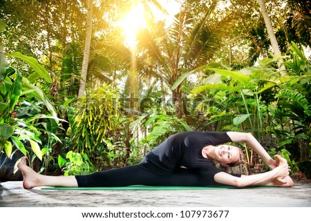 Yoga parivrtta janu sirsasana pose by smiling woman in black cloth in the garden with palms and banana trees - stock photo