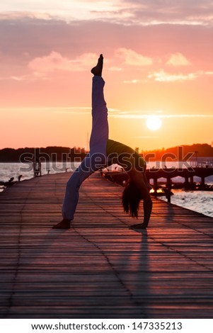 Yoga practice during sunset - stock photo