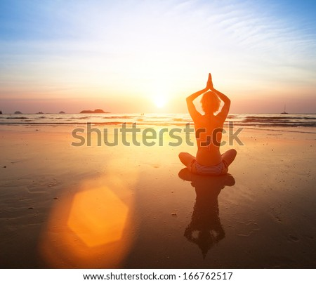 Yoga practicing at sunset, serenity and meditation. - stock photo