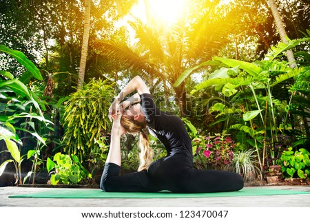 Yoga Raja Kapotasana pigeon pose by woman in black costume in the garden with palms, banana trees and plants in the pots - stock photo