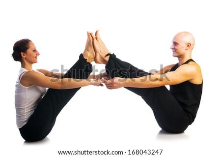 Yoga seria: Young couple in Navasana pose isolated on white background - stock photo