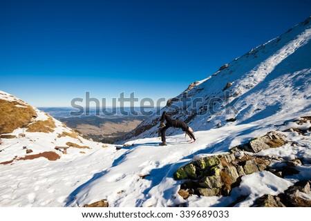 Yoga session in beautiful slovakian Belianske Tatry mountains. Beautiful sunny panorama - Siroka dolina - wide valley in snow - Chakra-asana, wheel pose - stock photo