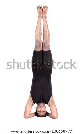 Yoga shirshasana headstand pose by Indian man in black costume isolated at white background. Free space for text - stock photo