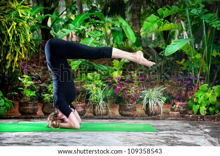 Yoga shirshasana headstand pose by young woman in black costume in the garden with banana trees and tropical plants in the pots - stock photo