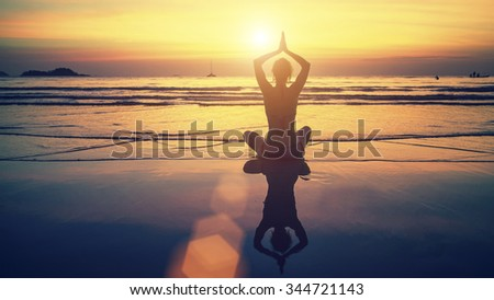 Yoga silhouette. Meditation girl on the background of the stunning sea and sunset. Woman doing meditation near the ocean.  - stock photo