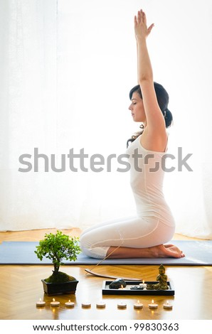 Yoga, stretching and meditation at home. Woman doing yoga pose with bonsai and candle indoor. Caucasian young model meditate. - stock photo