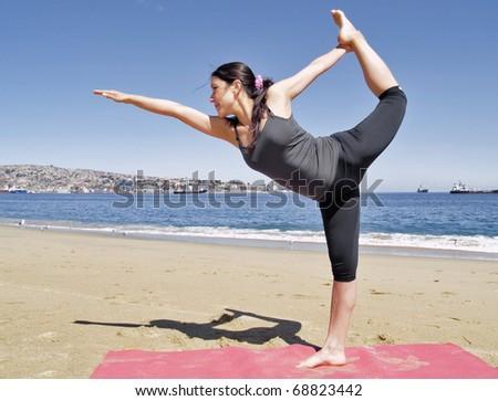 Yoga teacher practising at the beach pose dandayamana dhanurasana - stock photo