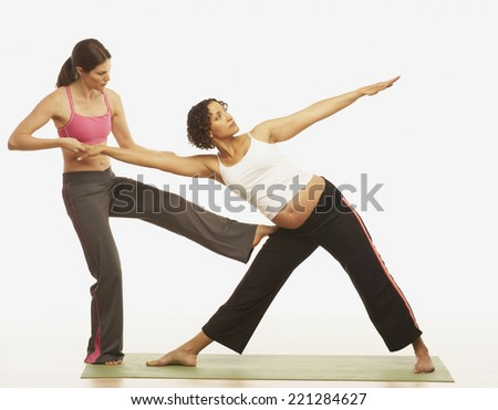 Yoga trainer assisting pregnant woman - stock photo