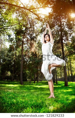 Yoga tree pose by woman in white costume on green grass in the park around pine trees - stock photo
