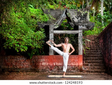 Yoga utthita hasta padangusthasana pose by man in white trousers near stone temple at sunset background in tropical forest - stock photo