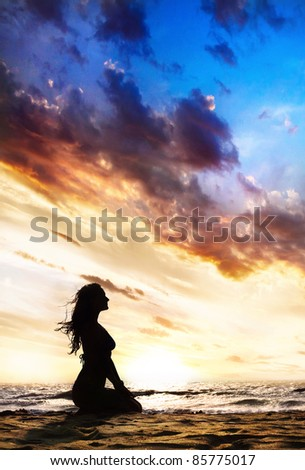 Yoga vajrasana thunder or diamond pose by beautiful Woman silhouette on the sand beach and ocean nearby at sunset background in India, Goa - stock photo