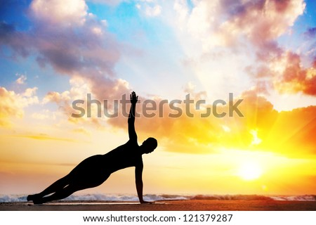 Yoga vasisthasana, side plank pose by woman in silhouette with sunset sky background. Free space for text - stock photo