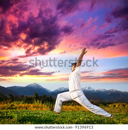 Yoga virabhadrasana I warrior pose by Indian Man in white cloth in the morning at mountain background - stock photo