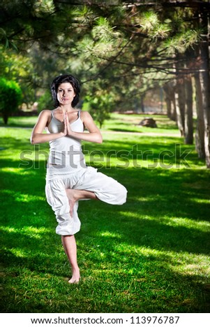 Yoga vrkshasana tree pose by woman in white costume on green grass in the park around pine trees - stock photo