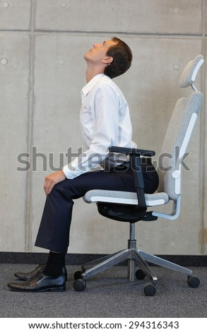 yoga with chair in office - business man exercising  - stock photo