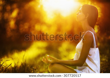 Yoga woman meditating at sunset. Female model meditating in serene harmony - stock photo