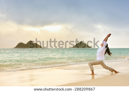 Yoga woman meditating in warrior pose relaxing outside on beach at sunrise. Female yoga girl working out training in serene ocean landscape. Lanikai beach, Oahu, Hawaii, USA. - stock photo