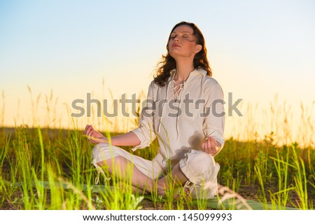Yoga woman meditating on green grass against the sun - stock photo