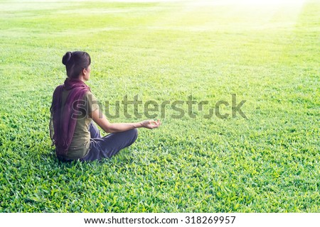 Yoga woman meditating outdoor in park on grass field background - stock photo