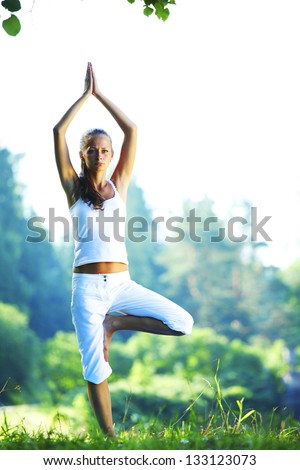 yoga woman on green park background - stock photo
