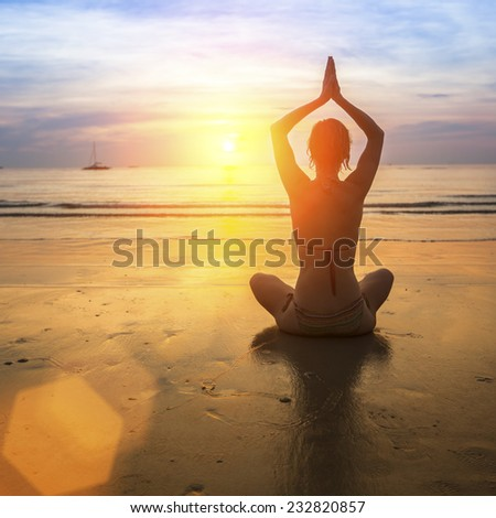 Yoga woman on the beach at amazing sunset. - stock photo