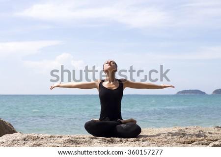 Yoga woman poses on beach near sea and rocks. Phuket, Thailand - stock photo