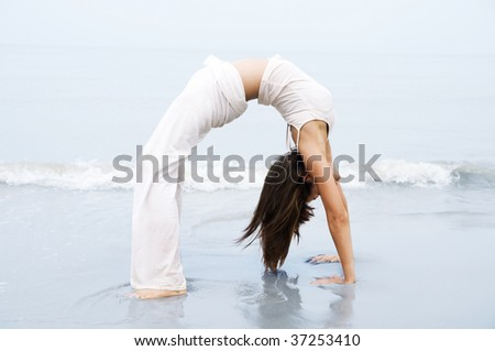 Yoga. Woman practicing Bridge Position Yoga on the beach. - stock photo