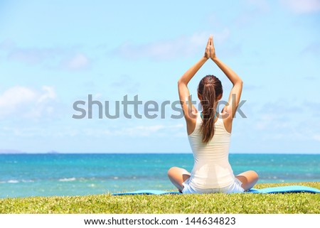 Yoga woman relaxing by sea doing the Sukhasana, easy pose facing water. Woman meditating in beautiful ocean landscape retreat. Meditation, yoga and relaxation concept. - stock photo