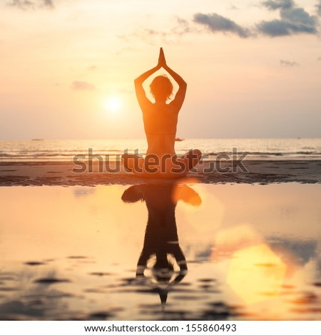 Yoga woman sitting in lotus pose on beach during sunset, with reflection in water (in bright colors) - stock photo