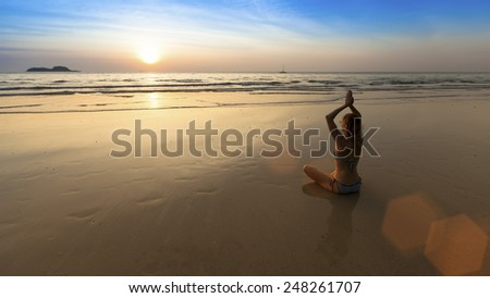 Yoga woman sitting in lotus pose on the beach during amazing sunset. Harmony. - stock photo