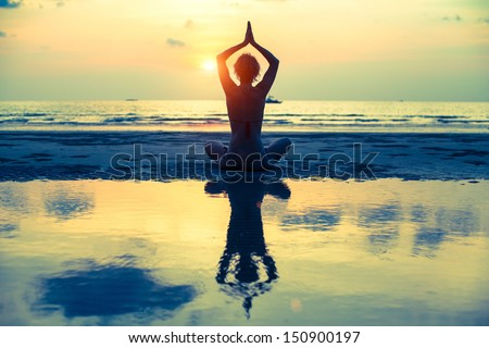 Yoga woman sitting in lotus pose on the beach during sunset, with reflection in water (cross-process style) - stock photo