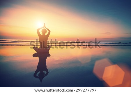 Yoga woman sitting in lotus pose on the beach with reflection in water during amazing sunset. - stock photo