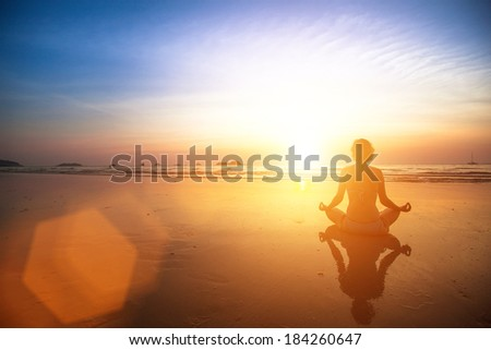 Yoga woman sitting on sea coast at sunset. - stock photo
