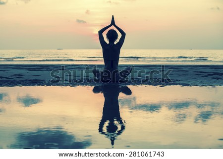 Yoga woman sitting on sea coast at sunset, silhouette, reflection and the sky in soft colours. - stock photo