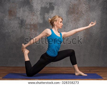 Yoga woman standing on one knee, copy space for text or slogan  - stock photo