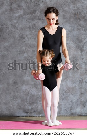 Yoga woman with little daughter exersizing together - stock photo