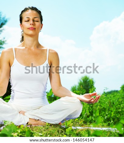 Yoga. Young woman doing yoga exercise outdoor - stock photo